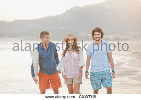 Friends walking together on beach - Stock Photo