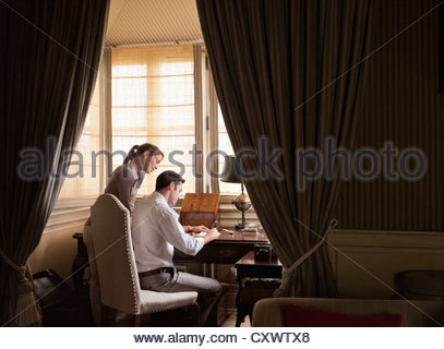 Couple writing at desk in study - Stock Photo