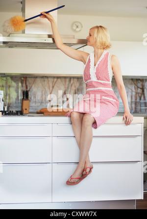 Woman dusting fan in kitchen - Stock Photo