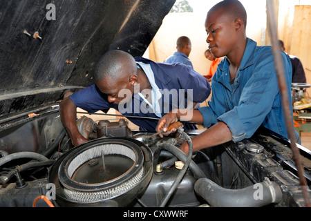 young mechanics works on a car engine. Machui Vocational Center, Machui, Zanzibar, Tanzania - Stock Photo