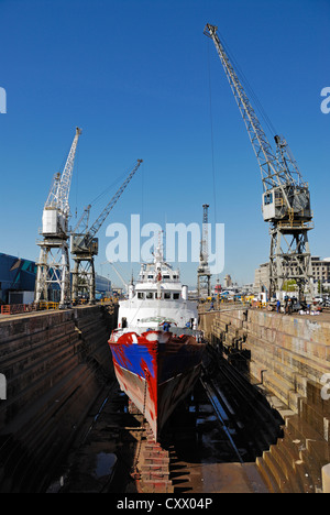 Ship being repaint in a dry dock, Cape Town, South Africa - Stock Photo