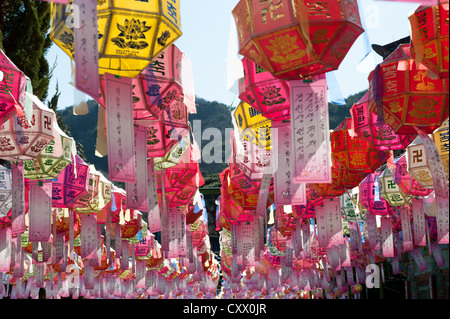 Busan, South Korea. Lanterns, with messages attached to them, hanging over a courtyard in the Buddhist Beomeosa - Stock Photo