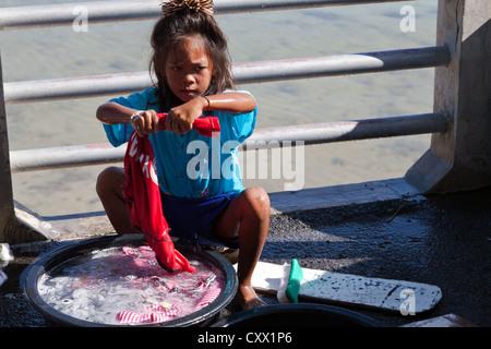 Little Sea Gypsy Children doing the Laundry at Rawai Beach in Phuket, Thailand - Stock Photo