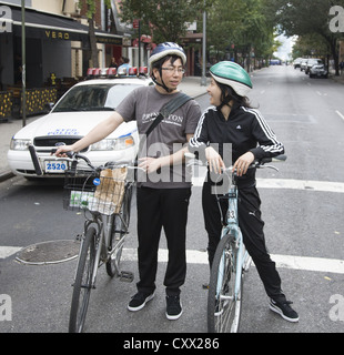 Young couple on bicycles waiting for the light to get on their way on the east side of Manhattan, NYC. - Stock Photo