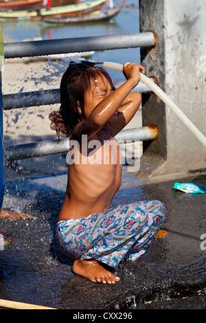 Little Sea Gypsy Girl washing herself at Rawai Beach on Phuket, Thailand - Stock Photo