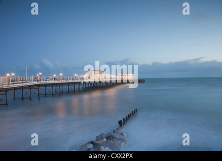 Evening view of Worthing pier, Sussex, illuminated at sunset, with rocks and groyne in foreground. - Stock Photo