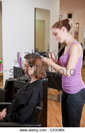 A female hairdresser colouring a female clients hair - Stock Photo