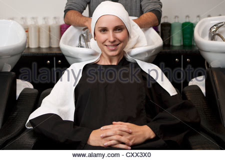 A female client sitting at a wash basin in a hairdressing salon - Stock Photo