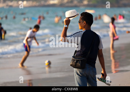 Man with white Hat on the Beach of Patong in Phuket, Thailand - Stock Photo
