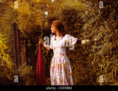 A woman in a white dress, standing in a garden and holding a long red scarf. - Stock Photo
