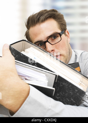 Stressed young businessman wearing glasses carrying document files, serious face, overworked - Stock Photo