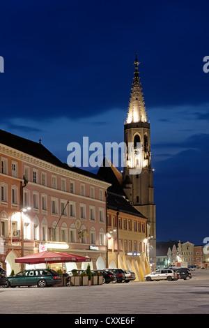 Ludwigstrasse street with Stadtplatz square and the parish church of St. Nikolaus, St Nicholas, dusk, Neuoetting, - Stock Photo