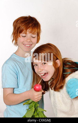 Girl and boy Boy feeding a radish to a girl - Stock Photo