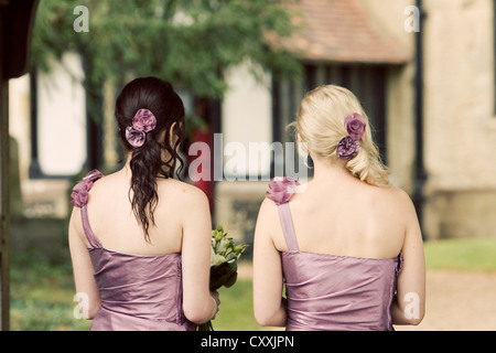 Two bridesmaids photographed from behind wearing one strap dusky purple dresses and matching flowers in their hair - Stock Photo