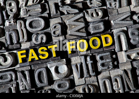 Old lead letters forming the word 'fast food' - Stock Photo