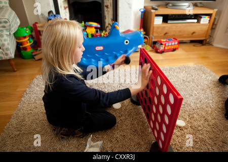 Child playing 'Connect Four' or 'Four in A Line' in living room. - Stock Photo