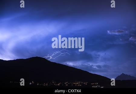 Ominous clouds and lightning bolts from thunderclouds over Mt. Patscherkofel near Innsbruck, night scene, Innsbruck, - Stock Photo