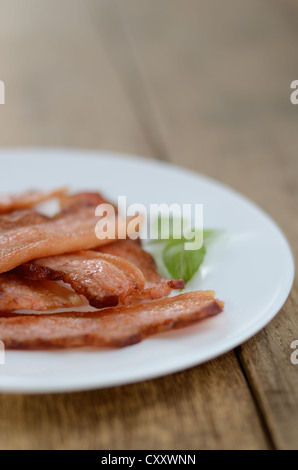 Fried bacon strips on the white plate - Stock Photo