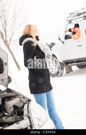 Woman having trouble with car snow assistance winter talking man - Stock Photo