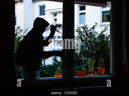 Burglar breaks into an apartment. Symbol image. - Stock Photo