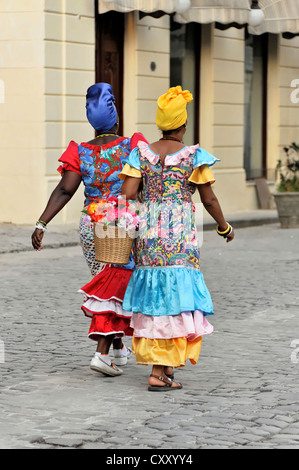 Two Creole women wearing colourful dresses walking in the centre of Havana, Cuba, Greater Antilles, Central America, - Stock Photo
