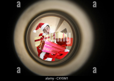View through a peephole to a man dressed as Santa Claus bearing Christmas presents - Stock Photo
