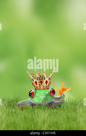 Frog wearing a golden crown sitting on the grass, waving, illustration - Stock Photo