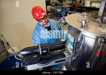 A chemist dressed in safety gear works in research at a at a pharmacutical research laboratory - Stock Photo