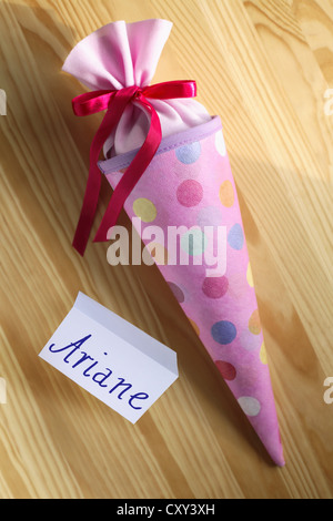 Pink schultuete or school cone filled with gifts and sweets beside a name tag for Ariane - Stock Photo