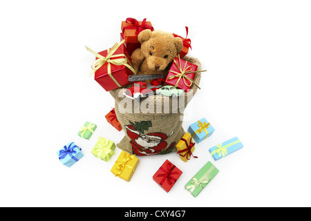 Christms sack filled with Christmas gifts, a teddy bear and toy cars - Stock Photo