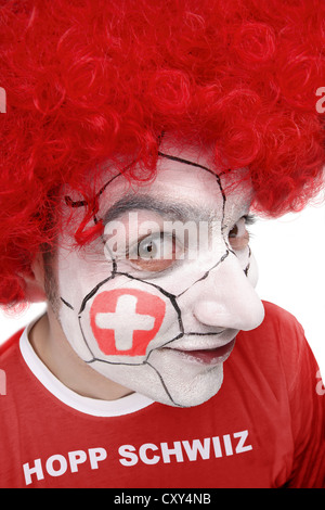 Young man, football fan with a painted face, Swiss national flag, wearing a red t-shirt, lettering 'Hopp Schwiiz' - Stock Photo