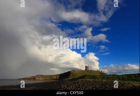 Dramatic light at Dunstanburgh Castle on the Northumberland coast, England. - Stock Photo