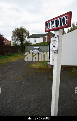 No Parking sign with parked car in background - Stock Photo
