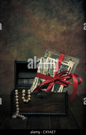 old photos with a bow in a chest with a pearl necklace - Stock Photo