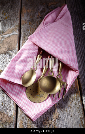 Old kitchen utensils made of brass wrapped in a kitchen towel, lying on a rustic wooden background - Stock Photo