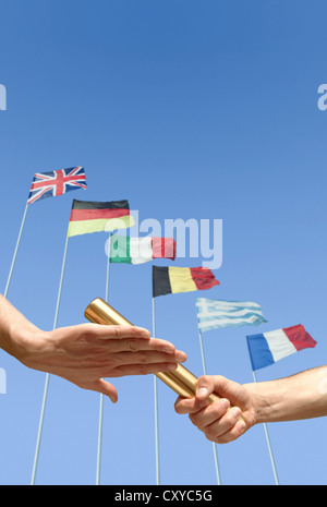 Relay race, detail of athletes hands during the handover of the baton in front of international flags - Stock Photo