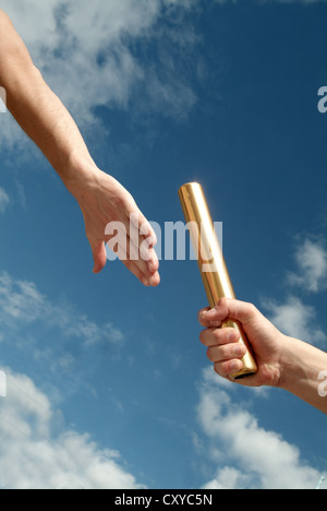 Relay race, detail of athletes hands during the handover of the baton - Stock Photo