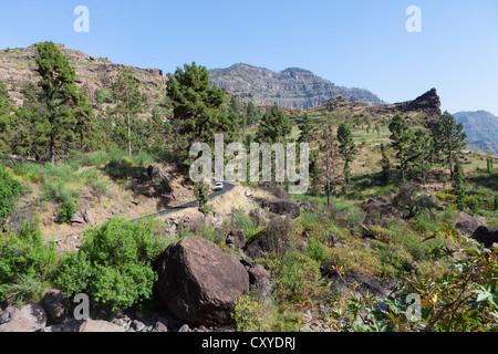 Mountain chain and a country road, El Pie de la Cuesta, Roque Bentaiga, Gran Canaria, Canary Islands, Spain, Europe - Stock Photo
