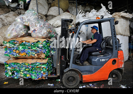 Forklift transporting compressed and packaged plastic bottles at a recycling plant for the export to China, San - Stock Photo