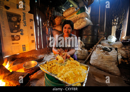 Woman preparing the traditional dish 'Bory Bory' in a simple kitchen on an open fire, soup with corn dumplings - Stock Photo