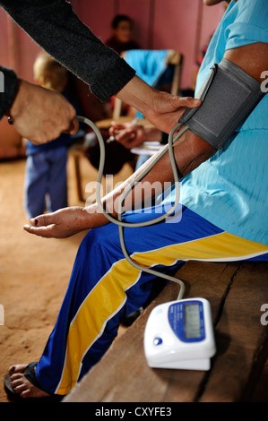 The blood pressure of a woman is being measured, by an aid organisation examining and advising mothers about health - Stock Photo