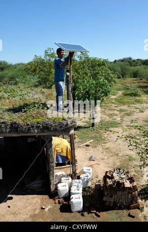 Young man mountain solar cells on the roof of a simple hut of a smallholder's farm, Gran Chaco, Santiago del Estero - Stock Photo