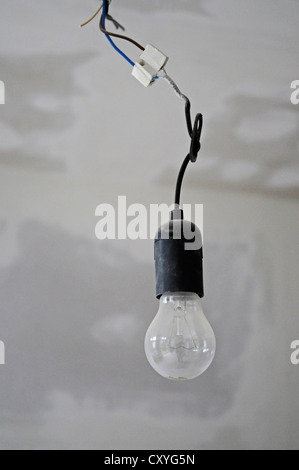 Single light bulb hanging from a ceiling, building renovation - Stock Photo