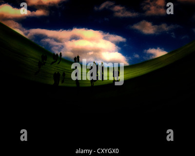 Silhouetted figures under a blue sky - Stock Photo