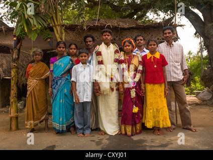 Young Bride And Groom Dressed For The Ceremony And Adorned With Flower Garlands Posing Surrounded By Family, Pondicherry, - Stock Photo