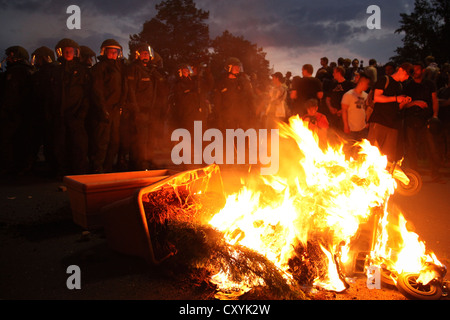 Police, protesters and a lit rubbish dumpster, end of the 'Revolutionary May 1st Demonstration' in Kreuzberg, Berlin - Stock Photo