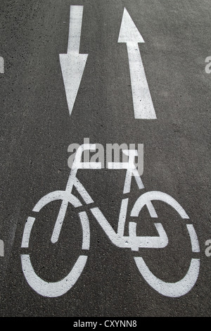 Cycle path, directional arrows, road markings on the asphalt - Stock Photo