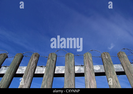 Wooden fence with barbed wire, against a blue sky - Stock Photo