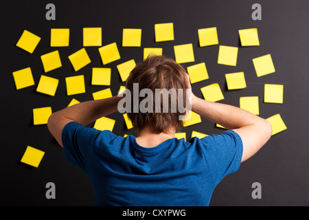 Young student with stress and looking to a board full of yellow notes - Stock Photo