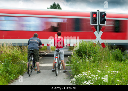 A man and a woman with bicycles standing at a closed railway crossing, Grevenbroich, North Rhine-Westphalia - Stock Photo